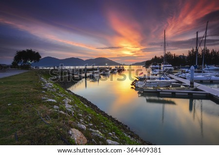 Beautiful composition view of Malaysian Harbour with a yatch during sunset. Noise slighty appear and soft focus due to long exposure. - stock photo
