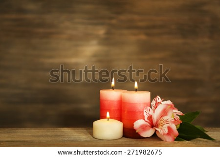 Beautiful composition with candles and spa stones on wooden background - stock photo