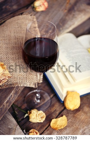 Beautiful composition with glass of wine with old book on table close up