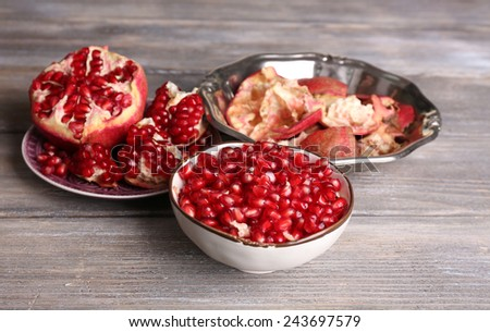 Beautiful composition with juicy  pomegranate seeds, on old wooden table - stock photo