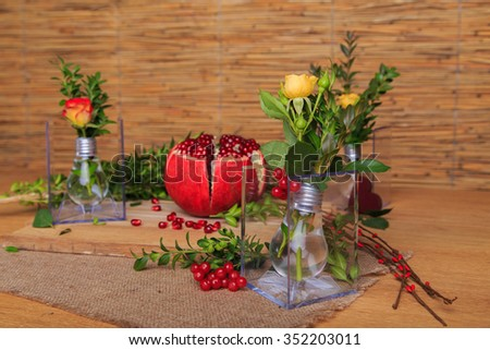 Beautiful composition with pomegranate, flowers and bulbs. Beautiful still-life with a pomegranate on the wooden background. Beautiful composition decor of fruits and flowers.