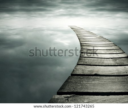 Beautiful conceptual background with a wooden path in to the infinity dramatic sky - stock photo