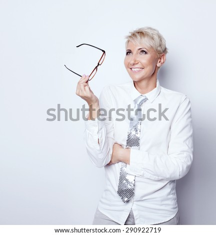 Beautiful confident blonde businesswoman holding eyeglasses, smiling, posing in studio. - stock photo