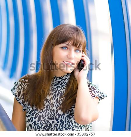 Beautiful confident businesswoman indoor glass corridor talking by phone - stock photo