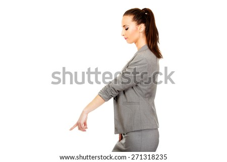 Beautiful confident businesswoman pointing down. - stock photo