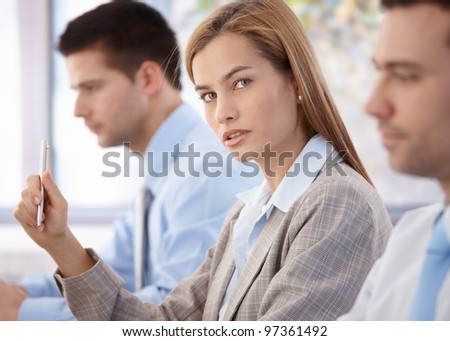 Beautiful confident businesswoman sitting at business meeting.?
