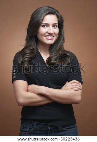 Beautiful confident friendly young woman on brown background - stock photo