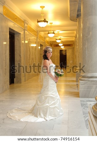 beautiful contemporary bride standing with bouquet - stock photo