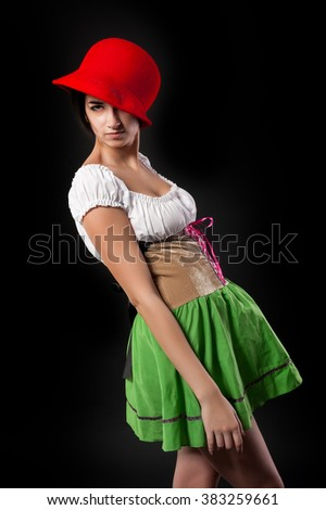Beautiful cool woman in german beer girl costume with red hat. Isolated on black - stock photo