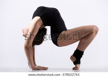 Beautiful cool young fit gymnast athlete woman in black leotard doing art gymnastics pose, backward extension acrobatic exercise on tiptoes, full length, studio, white background, isolated - stock photo