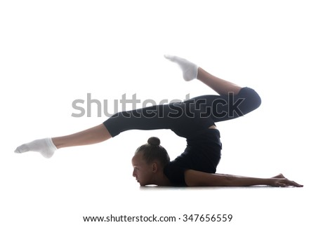 Beautiful cool young fit gymnast athlete woman in sportswear doing art gymnastics, backbend acrobatic exercise, full length, studio, dark background - stock photo