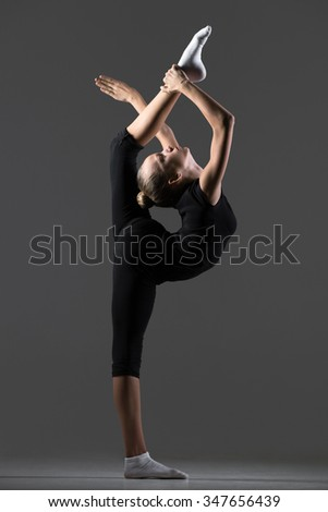 Beautiful cool young fit gymnast athlete woman in sportswear working out, dancing, doing back scale, balance rhythmic gymnastics exercise, standing backbend, full length, studio, dark background - stock photo
