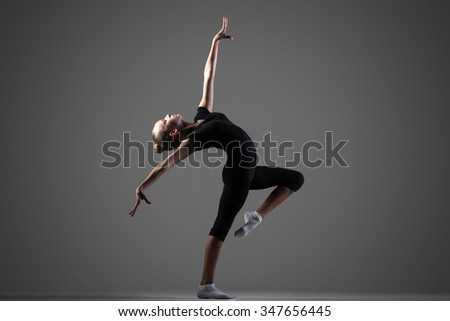 Beautiful cool young fit gymnast athlete woman in sportswear working out, dancing, doing passe with backbend, balance art gymnastics exercise, full length, studio, dark background - stock photo