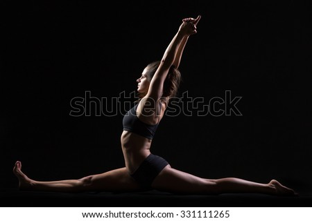 Beautiful cool young fit woman in sportswear doing sport exercise, sitting in full split, Monkey God posture, Hanumanasana, side view, studio, black background - stock photo