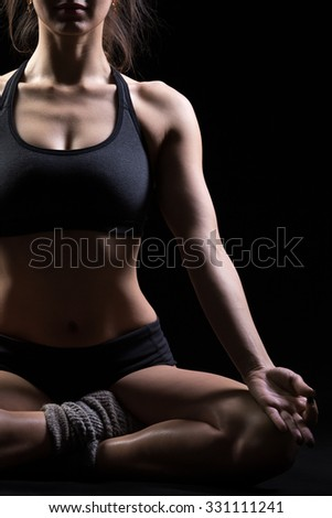 Beautiful cool young fit woman in sportswear practicing yoga, sitting in Sukhasana, Easy Posture, meditating, breathing, front view, studio, black background, close up - stock photo