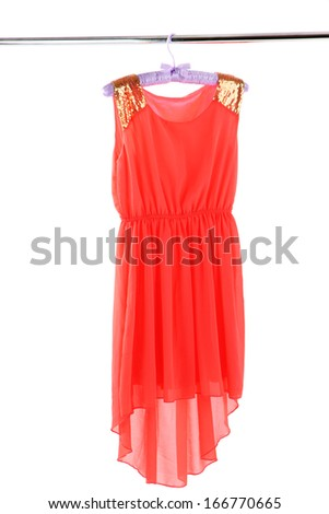 Beautiful coral dress hanging on hangers isolated on white