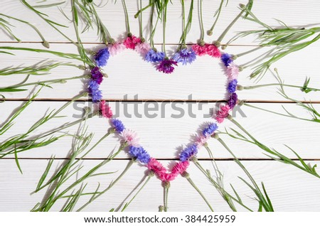 Beautiful cornflowers in shape of heart on wooden background - stock photo