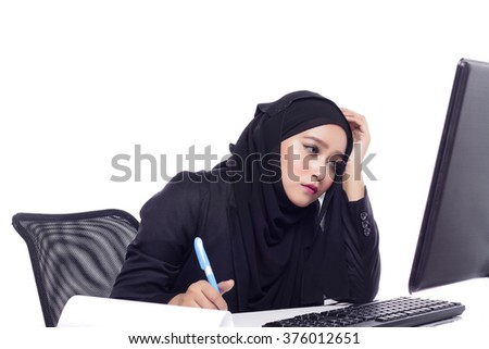 beautiful corporate muslimah woman with office attire showing a tired expression working at desktop computer - stock photo
