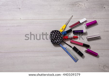 Beautiful cosmetic bag with polka dots with make-up copyspace  on a wooden background . Lipsticks and nail polishes - stock photo