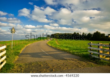 beautiful country road in the netherlands early in the morning - stock photo
