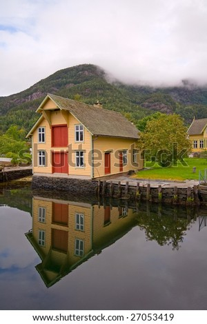 Beautiful countryside house reflected in a fjord lake, Norway - stock photo