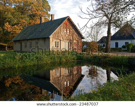 Beautiful countryside house reflected in a lake Denmark - stock photo