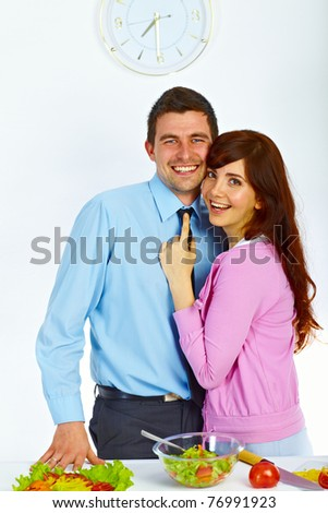 Beautiful couple are hugging and smiling on the kitchen - stock photo