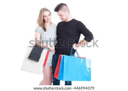 Beautiful couple at shopping carrying gift bags and paying with debit card isolated on white background with copyspace