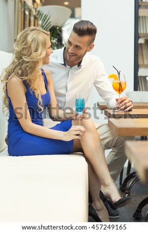 Beautiful couple at the bar drinking cocktails