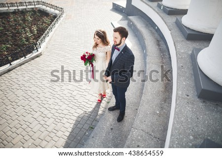 Beautiful couple, bride and groom posing near big white column