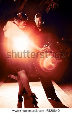 Beautiful couple dancing tango on night street, dramatic light. - stock photo