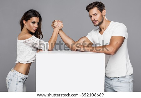 Beautiful couple doing arm wrestling challenge - stock photo