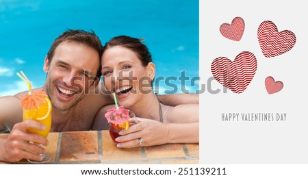 Beautiful couple drinking cocktails in the swimming pool against cute valentines message - stock photo