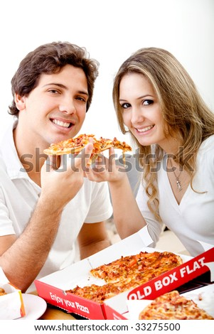 Beautiful couple eating pizza isolated over white
