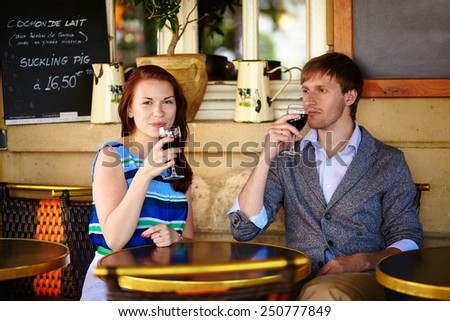 Beautiful couple enjoying their red wine in a cafe