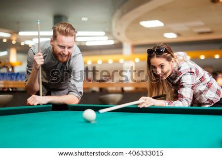 Beautiful couple flirting while playing snooker - stock photo