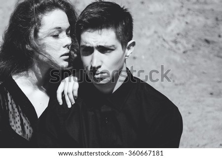Beautiful couple. Girl whispers something in the ear of young man, black and white portrait - stock photo