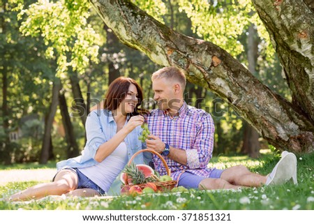 Beautiful couple having a lovely picnic in the summer park eating fruits.