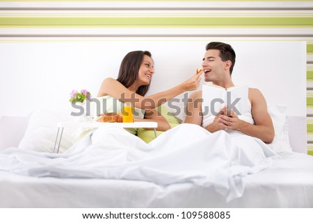 beautiful couple having breakfast in bed, girl feeding her boyfriend - stock photo