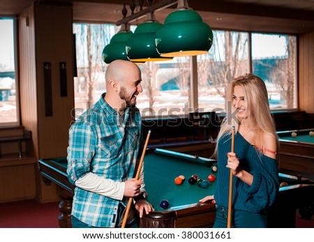 Beautiful couple having fun and playing billiards. Billiard sport concept. American pool billiard. Pool billiard game. - stock photo