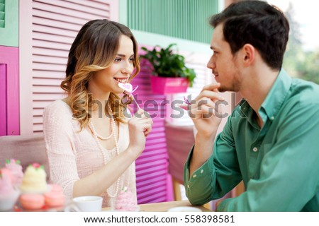 Beautiful  couple having fun licking heart lollipops on their first date