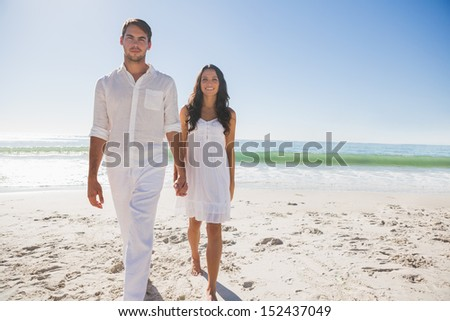 Beautiful couple holding hands and walking towards camera at the beach - stock photo