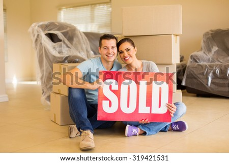 beautiful couple holding sold sign surrounded by cardboard boxes - stock photo