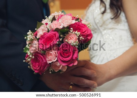 Beautiful Couple holding wedding flowers bouquet. Detail
