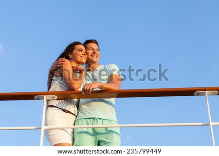 beautiful couple hugging and looking into the distance on cruise - stock photo