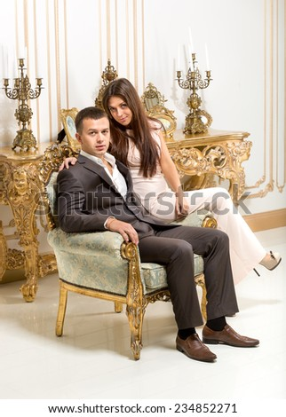 Beautiful couple hugging on chair at luxurious classic interior - stock photo