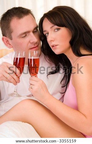 Beautiful couple in bed drinking wine.