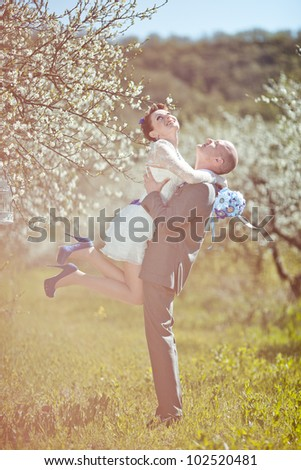 beautiful couple in blooming tree in spring - stock photo