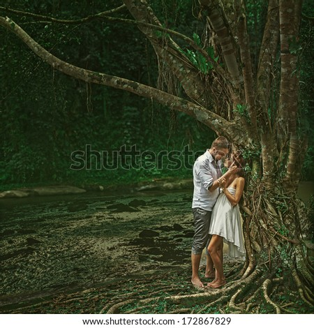 Beautiful couple in dramatic forest - stock photo