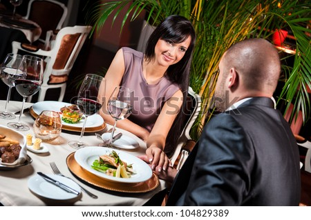 Beautiful couple in love at restaurant - stock photo